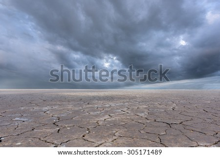 storm clouds and dry soil - stock photo