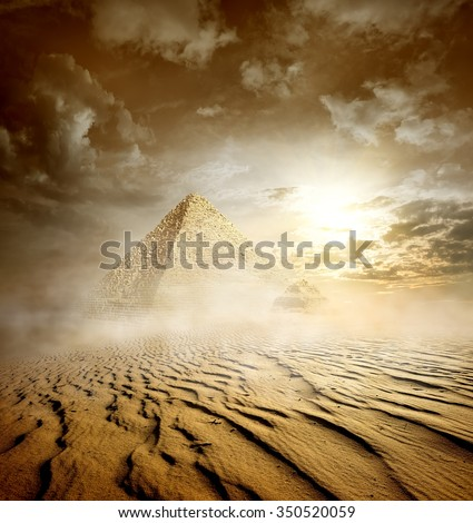 Storm clouds and pyramids in sand desert - stock photo