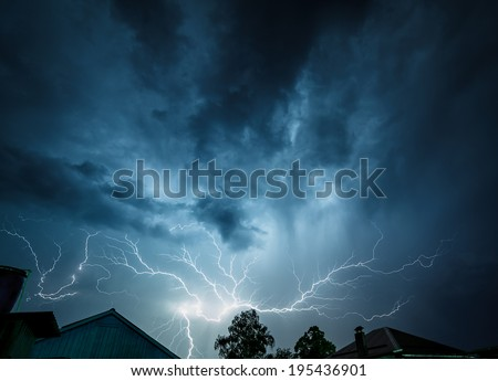 Storm clouds are illuminated from within a flash of lightning.