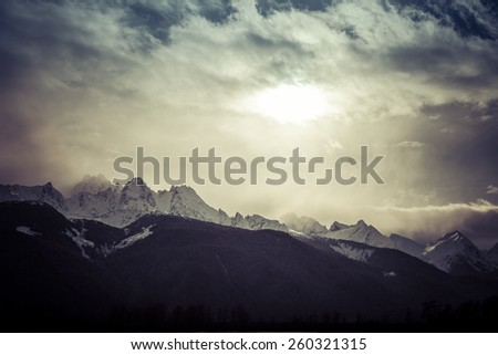 Storm clouds covering the sun over Cathedral Peaks in Southeast Alaska. - stock photo