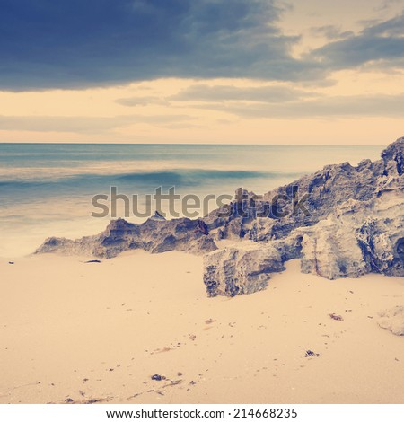 Storm clouds creep in over the ocean with rocks and sand - stock photo