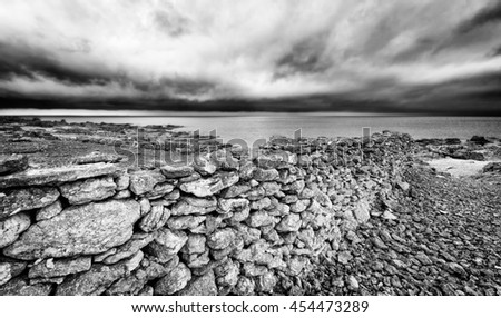 Storm clouds gather off the rocky coast of Faro, a Swedish island in the Baltic Sea. A mysterious old stone wall leads to the water's edge. Black and white image. - stock photo