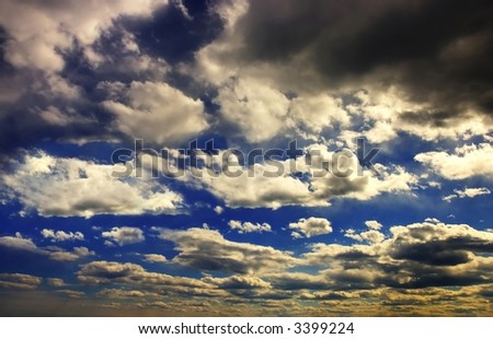 Storm clouds gathering on bright blue sky, around sunset - stock photo
