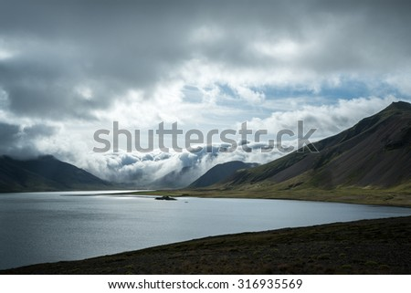 storm clouds, mountains, valleys and lake on a summer afternoon in Iceland  - stock photo