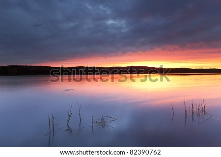 Storm clouds over a calm lake, Dalarna, Sweden - stock photo