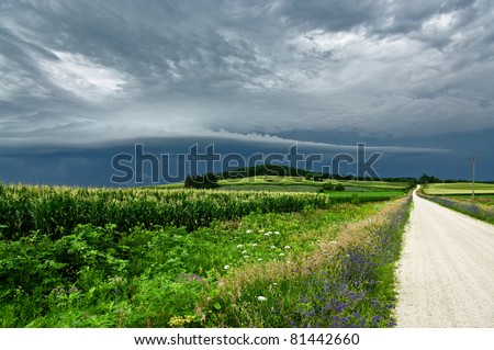 Storm Clouds Over a Country Road:  Gray clouds gather before a summer storm in northeast Iowa. - stock photo