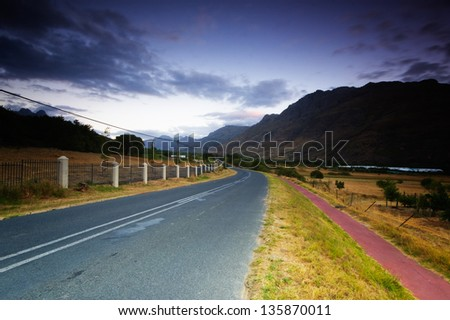 storm clouds over a road stretching into the distance, stellenbosch, south africa. Dramatic post production. - stock photo