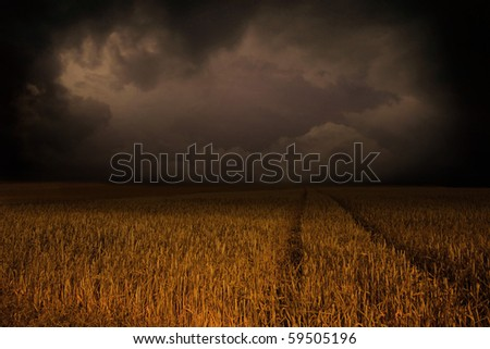 Storm clouds over field - stock photo