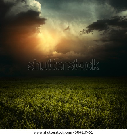 Storm clouds over green meadow with grass - stock photo