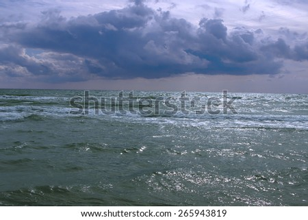 Storm clouds over the raging sea in summer