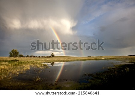Storm Clouds Saskatchewan with rainbow reflection in water