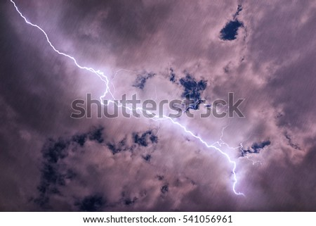 Storm clouds with lightning discharge and diffuse streams of rain
