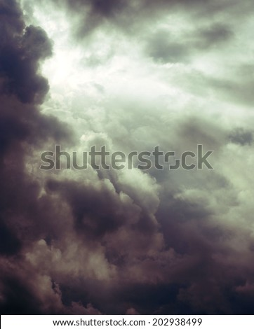 Storm clouds with sun trying to come through with instagram effect filter applied. Vertical image with sun in upper left corner and sun's rays coming down across the image from behind the thunderstorm - stock photo