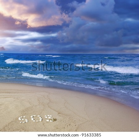 "storm coming - sandy beach with a word ""SOS"" written with seashells and dark clouds over the waves - stock photo"
