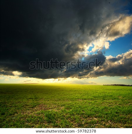 Storm dark clouds and sunlight over field with green grass