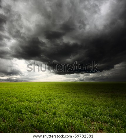 Storm dark clouds flying over field with green grass - stock photo