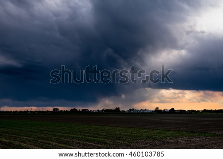 Storm dark clouds over field.Dramatic sky with stormy clouds, atmosphere of thunderstorm  - stock photo