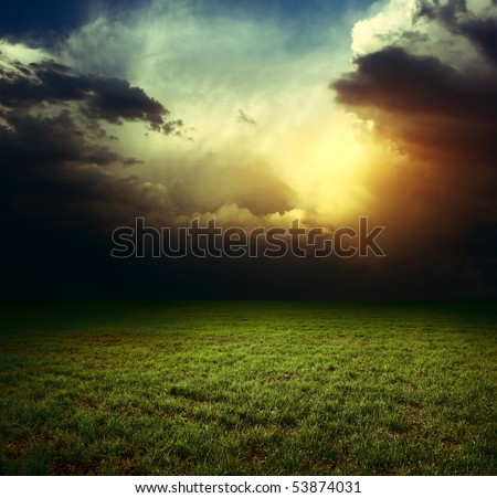 Storm dark clouds over field with grass - stock photo