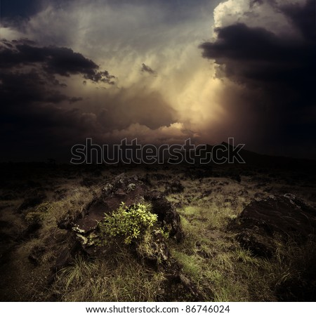Storm dark clouds over volcanic valley with grass and rocks. Mountain Agung in Bali. Indonesia - stock photo