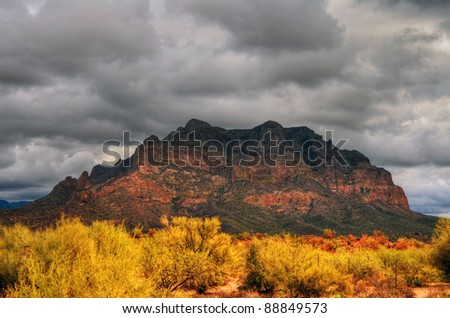 Storm forming over a rugged desert mountain - stock photo