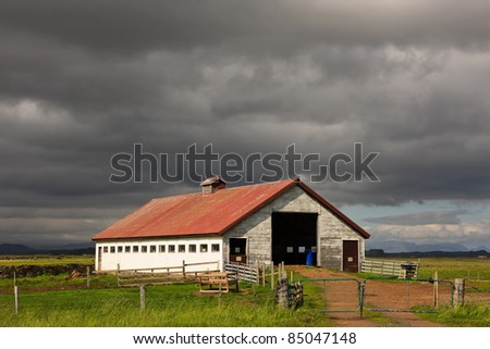 Storm looming over a farm in Iceland - stock photo