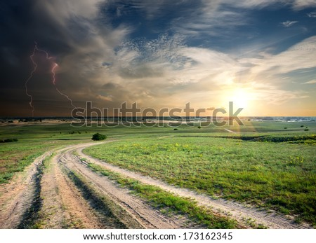 Storm over the country road in field - stock photo