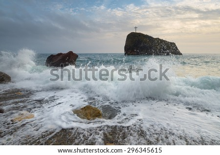 Storm sea with beautiful waves. Seascape with a rock. Christian cross on the cliff. Cloudy day, the bad weather. Crimea - stock photo