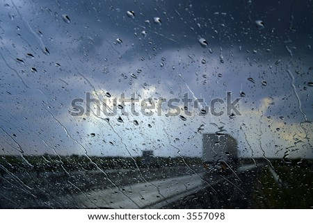 Storm seen through the windshield, with big rain drops - stock photo