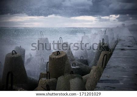 Storm surf breaking on breakwater. - stock photo