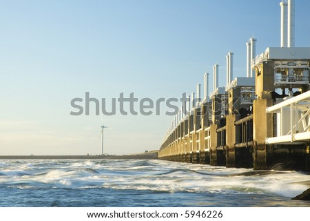 Storm surge barrier in Zeeland, Holland. Build after the storm disaster in 1953. Long shutter speed, waves are flowing. - stock photo