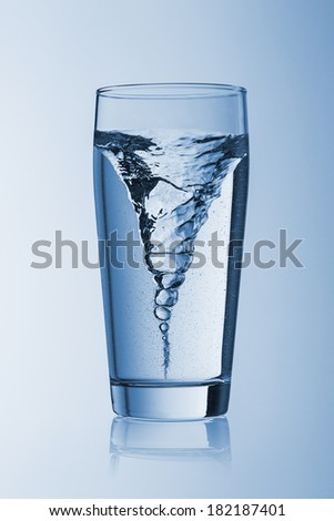 Storm tornado twister typhoon vortex in a water glass drinking on blue background - stock photo