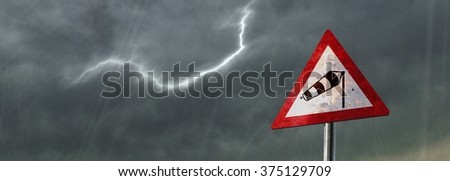 Storm warning sign in front of a stormy sky