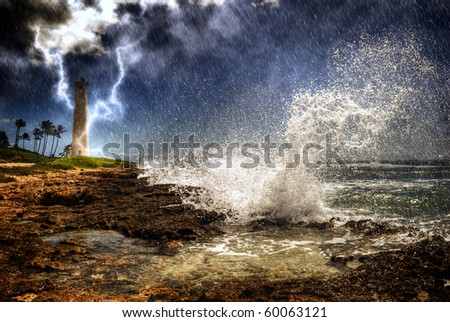 Storm wave lightning weather rain coast tropical island. Large wave crashing into rocky coast as rain pours down, lightning striking Barber's Point Lighthouse in the distance, Oahu Hawaii. - stock photo