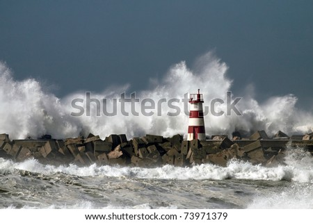 Storm waves over beacon of the harbor of Povoa do Varzim, Portugal - stock photo