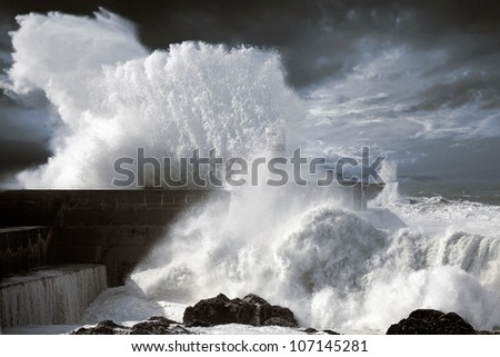 Storm waves over beacon of the harbor of river Douro, Portugal - enhanced sky - stock photo