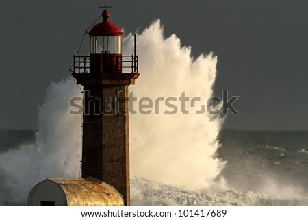 Storm waves over lighthouse of the harbor  of river Douro, Portugal; end of the day light. - stock photo