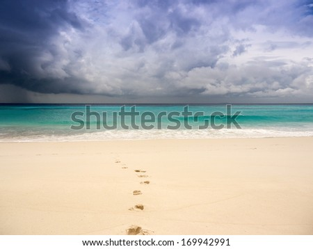 Stormy beach with footprints on the sand - stock photo