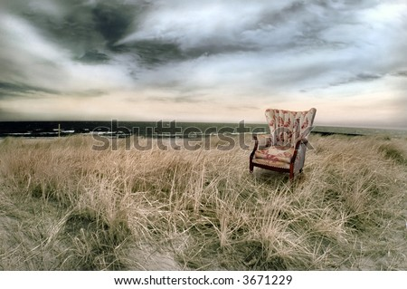 Stormy beach with wing-back chair in infrared.
