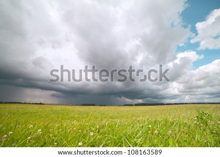 Stormy cloud over green land.