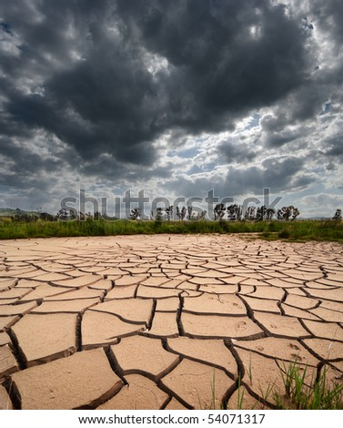 stormy clouds dark are gathering on dry and cracked land - stock photo