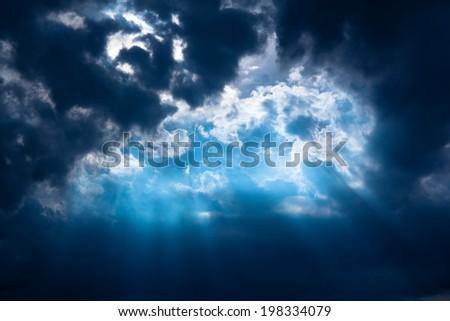 Stormy dark-blue sky with a dramatic sunbeam  - stock photo