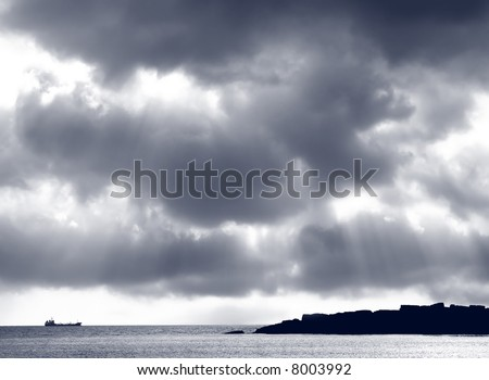 Stormy dark clouds with sun rays passing through - stock photo