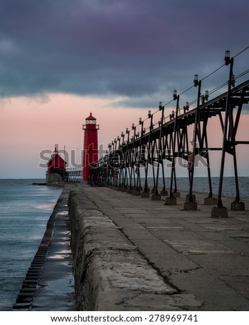 Stormy dawn at the Grand Haven South Pierhead Inner Light with Entrance Light in background in Grand Haven State Park in Grand Haven, Michigan - stock photo