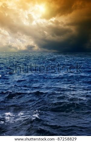 Stormy deep blue sea, dark sky, sun shines through clouds - stock photo