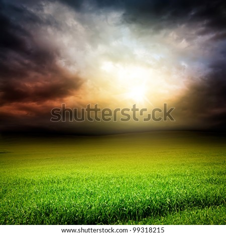 stormy dramatic sky and green field of grass with sun light passing through the clouds in the evening - stock photo