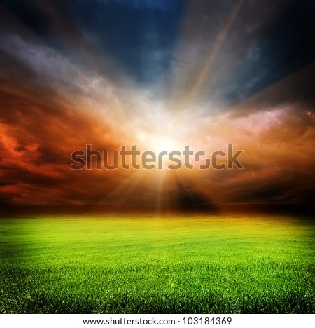 stormy evening clouds in the sky and green field of grass with sun light passing through - stock photo