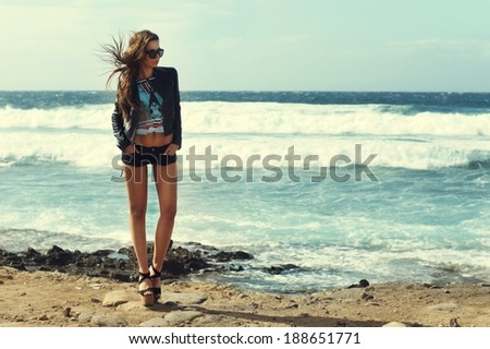 Stormy fashion photo. Beautiful and sexy girl at windy sea coast.          - stock photo