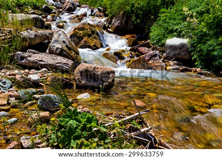 Stormy mountain river with a stone in the foreground