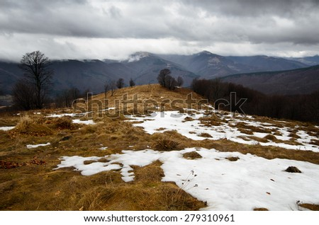 Stormy mountains with snow peaks on distance - stock photo