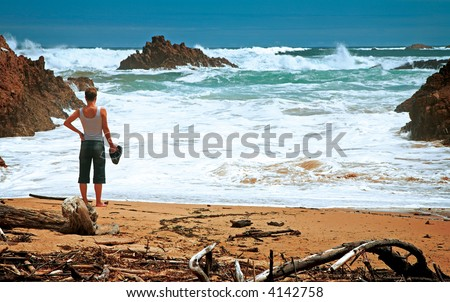 Stormy ocean view with a woman standing on the sand beach, evening in Knysna, South Africa - stock photo